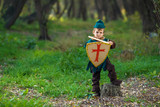 Cute little boy dressed as a knight playing with a sword and a shield in the forest
