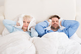 Fototapety Couple Covering Ears While Sleeping On Bed