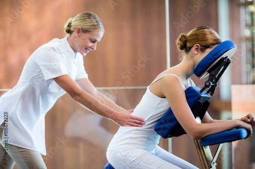 Woman receiving massage in massage chair