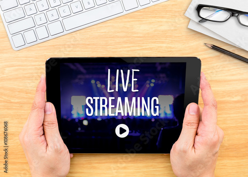 Hand holding tablet with Live Streaming word on wood table ,Inte Poster