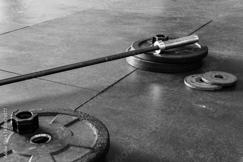 Barbell and weights on a gym floor, in black and white