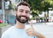 Mann mit Bart in der Stadt zeigt Daumen