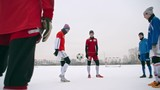 Group of teenage soccer players juggling a ball on snow-covered field in winter
