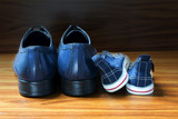 Men shoes and children sneakers side by side on the wooden floor, father's day - 108736233