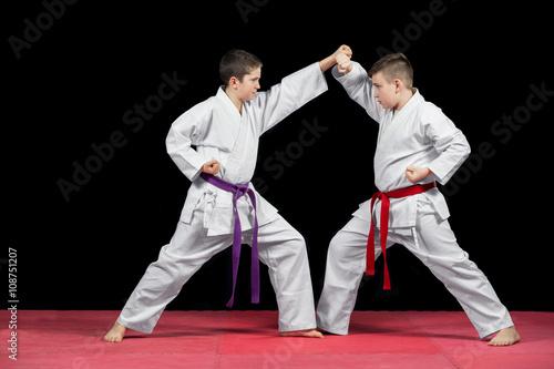 Fototapeta Two boys in white kimono fighting isolated on black background