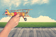 Quadro woman's hand holding toy airplane against blue sky