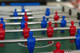 Players of the game of Foosball in red and blue color