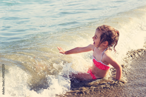 Toned portrait of Cute little girl sitting and smiling at ocean beach