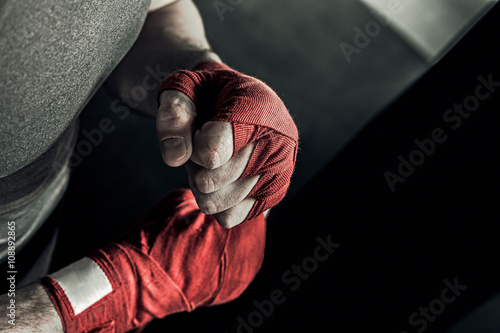 Closeup male hand of boxer with red boxing bandages Poster