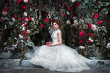 Luxury bride is sitting on the terrace in the mysterious garden of roses twined