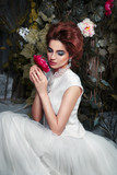 Luxury bride sitting in a mysterious garden wreathed with roses and holding a flower in the hands