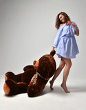Young beautiful girl with big teddy bear soft toy happy smiling