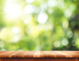 Fototapety Empty brown wood table top with sun and blur green tree bokeh ba