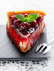 piece of cherry cheesecake and leaves of fresh mint