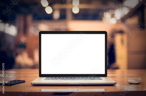 Laptop with blank screen on table.