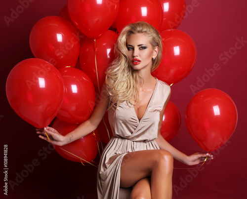 sexy woman with blond curly hair wears elegant dress, holding a lot of red air balloons
