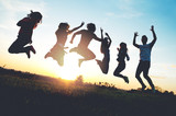 Group of people jumping outdoors; sunset