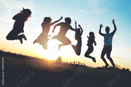 Póster Group of people jumping outdoors; sunset