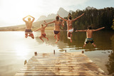 Fototapety Young friends jumping into lake from a jetty