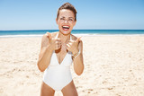 Smiling woman in white swimsuit at sandy beach showing thumbs up