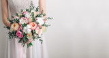 Beautiful wedding bouquet in hands of the bride. Peony rose, cotton, roses. Pink and Peach. Trendy and modern wedding flowers. Ideal photo for commercial. Space for your logo - 108983053