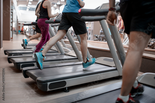 Poster People running in machine treadmill at fitness gym club