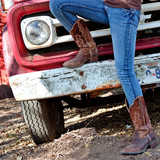 Western style image of cowgirl's legs in jeans and boots and old Texas truck on background - 109001853
