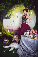 Little girl as Alice in Wonderland and evil queen
