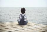 niño pensativo mirando el mar - 109024401