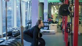 Young woman with beautiful sportive body fails to raise heavy dumbbell in gym close up