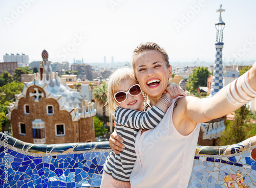 Smiling mother and baby taking selfie at Park Guell, Barcelona