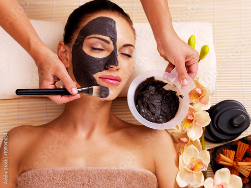 Kosmetolog rozmazuje kosmetyczną maskę na twarzy kobiety