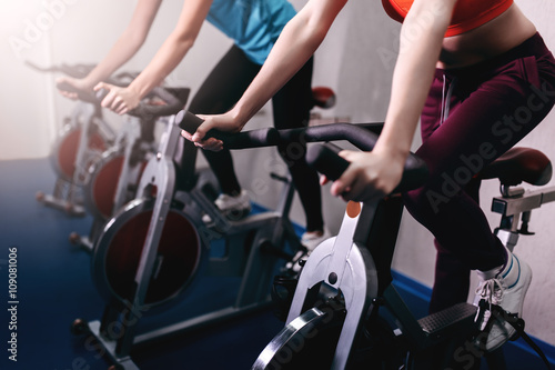Poster Woman on fitness exercise bike at indoor