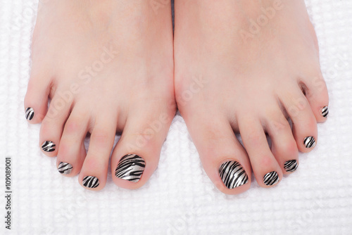 Papiers peints Pedicure Close-up shot of beautiful woman feet with pedicure coloring Zebra
