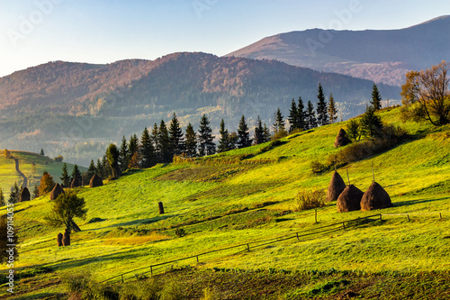 agricultural field with haystack on hillside at sunrise © Pellinni
