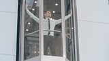 Young businessman standing in the moving up glass elevator and looking at the business center