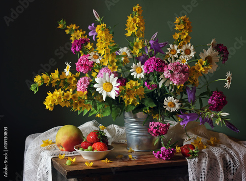 Still life with a summer bouquet and fruits.