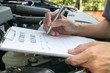 Mechanic Inspecting damage car and filling in accident report fo