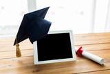 close up of tablet pc with mortarboard and diploma
