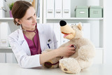 Beautiful smiling female doctor in white coat examine teddy bear