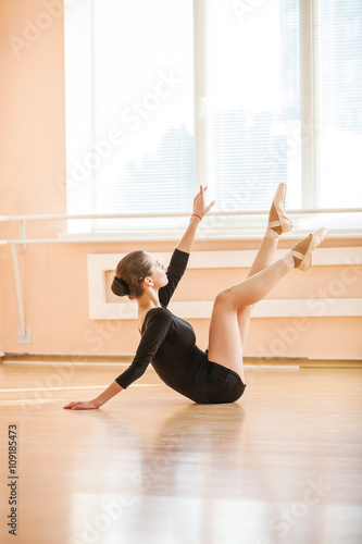 Young ballet dancer performing exercise while sitting on floor  © Andrey Bandurenko