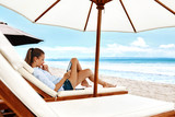 Woman Reading E-book Relaxing On Lounger Under Tent On Beach