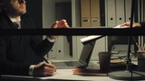 CEO working late in his cabinet; he taking document from secretary and signing it
