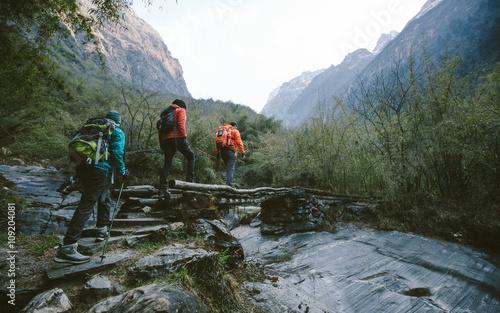 Group of trekkers cross the bridge