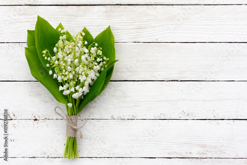 bouquet of lilies of the valley flowers with green leaves tied with twine in the water droplets on the white wooden boards Poster