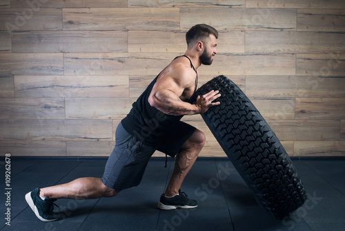 Poster Muscular man with tattoos and beard  pushing a tire in a black tank top and grey