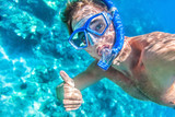 Snorkeling man underwater giving thumbs up ok signal wearing snorkel and mask having fun on beach summer holidays vacation enjoying recreational leisure time swimming in the sea. - 109278414