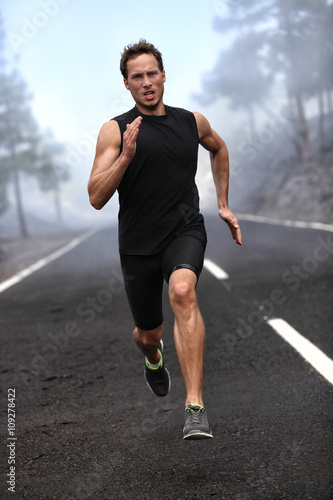 Naklejka Running runner man sprinting workout on mountain road. Jogging male fitness model working out training for marathon on forest road in amazing nature landscape.