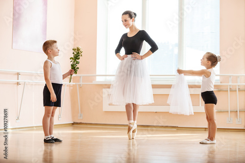 At ballet dancing class: young boy and girl giving flowers and veil to older student while she is dancing en pointe © Andrey Bandurenko