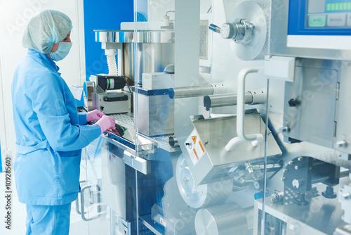 Papiers peints Pharmacie Pharmaceutics. Pharmaceutical worker operates blister packaging machine